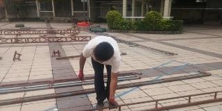 深圳广场上,几名工人在搭建舞台,搬运铁架捆扎铁丝,细致认真